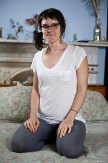 Позирование стройной тёлки в очках и в колготках на кровати